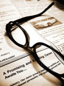 """Glasses resting on newspaper with text """"Promising Career"""""""