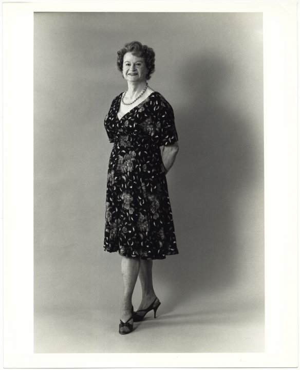In a black and white photograph, Virginia Prince, a white woman, poses standing. She holds her hands behind her back and turns out one foot. She is wearing a flowered dress, a string of pearls, and heels. She smiles.