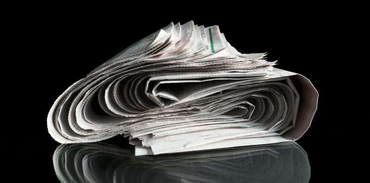 Rolled up newspaper on black background