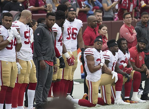 Some members of the San Francisco 49ers kneel during the National Anthem before a game against the Washington Redskins at FedEx Field on October 15, 2017 in Landover, Maryland. Source: Keith Allison (Wikimedia Commons).