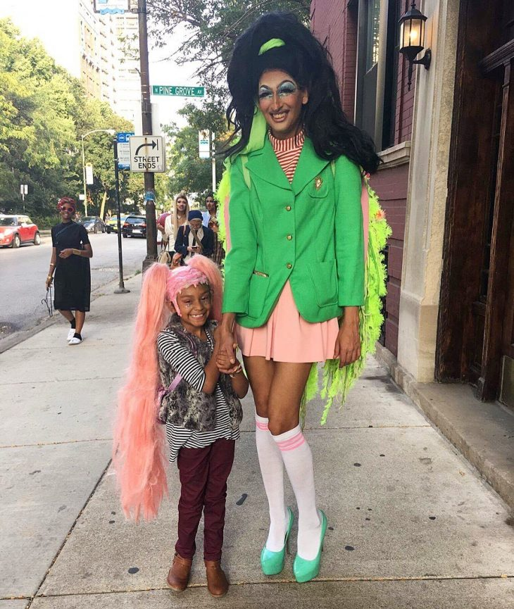 Abhijeet, a tall drag queen in a huge black wig, bright green jacket and pale pink skirt, stands holding hands with a young girl who's wearing a long, pink wig and a huge smile.