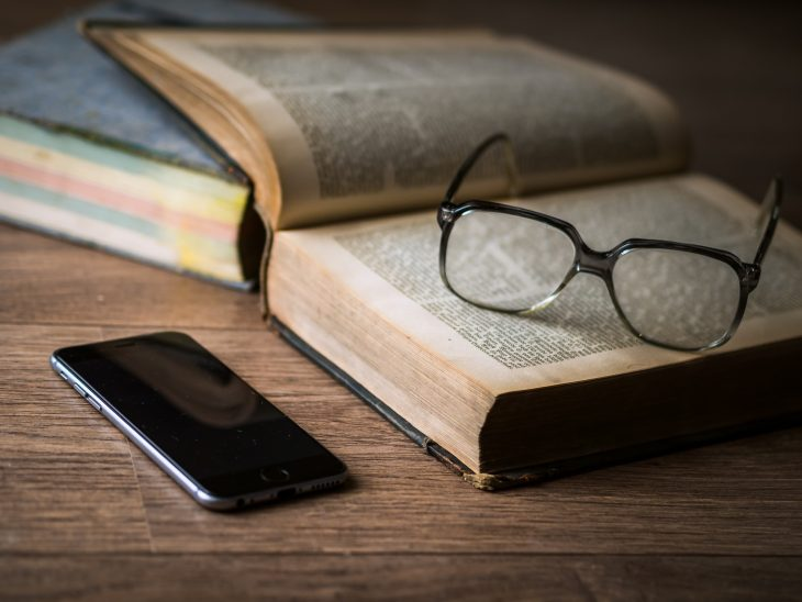 A smartphone sits on a table next to an open book. A pair of eyeglasses rests on the book.