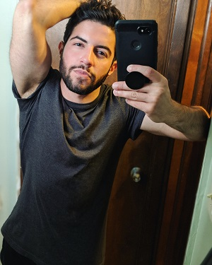 A selfie of Elliot Wake, a fit white man with dark hair and a short beard, wearing a loose gray t-shirt.
