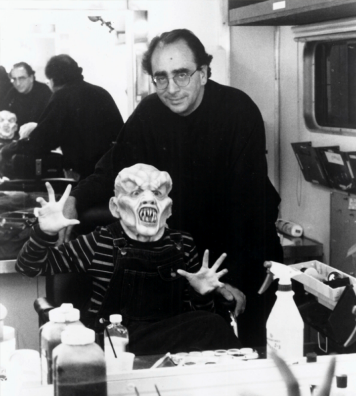 R.L. Stine stands behind a seated masked creature, preparing to shoot the Goosebumps series.
