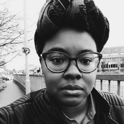 A headshot of Rivers Solomon standing on a city sidewalk. They are dark-skinned and wearing plastic-rimmed glasses with their braided hair wrapped and tied on top of their head.