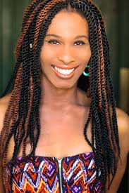Lady Dane Figueroa Edidi smiles at the camera. She is an Afro-Latina trans woman with her hair in long twists and a colorful strapless top.