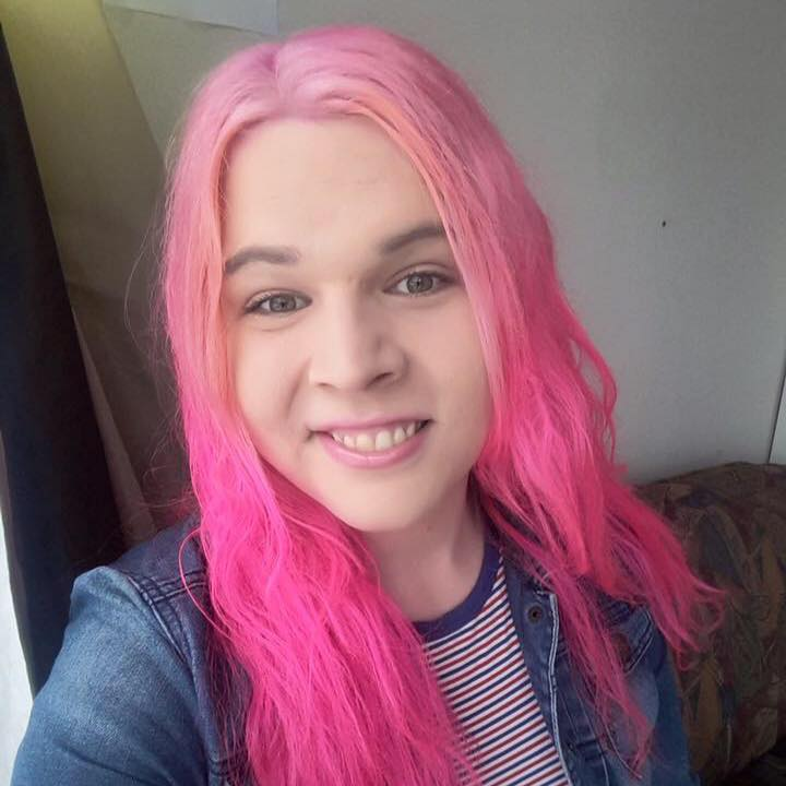 This selfie shows Sophie Labelle, a pale-skinned woman with long pink hair, smiling up at the camera.