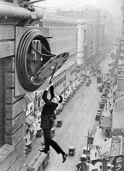 Harold Lloyd's character in the film Safety Last hangs from a clocktower over a busy street, looking alarmed.
