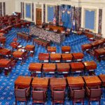 the US Senate chamber floor, with a blue patterned rug and brown desks arranged in a semicircle pattern facing the desks of the Senate leadership.