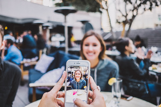 A person takes a picture of a woman at a busy restaurant with an iPhone