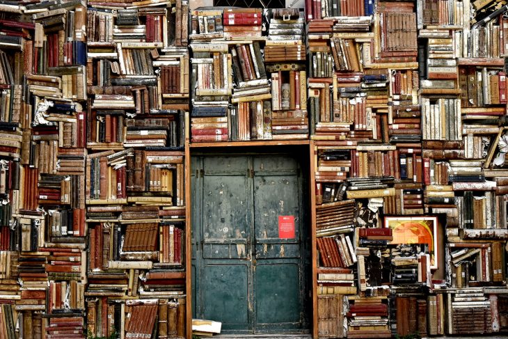 Crowded bookshelves surrounding a closed metal door.