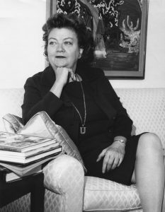 Ursula Nordstrom, editor and writer of children's books, in a black dress, sitting on a white couch looking off to the left. Undated; photo by Sidney Fields. Source: HarperCollins.com.