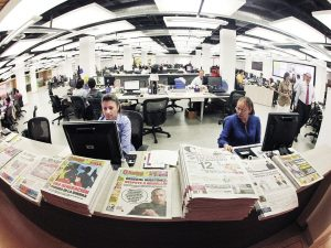 Modern-day newsroom, with people on computers and small stacks of printed newspapers on the front desk