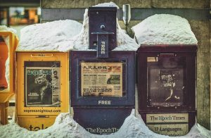 Three newspaper machines covered in snow