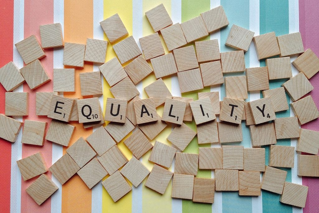 Equality spelled out in Scrabble squares on a rainbow background
