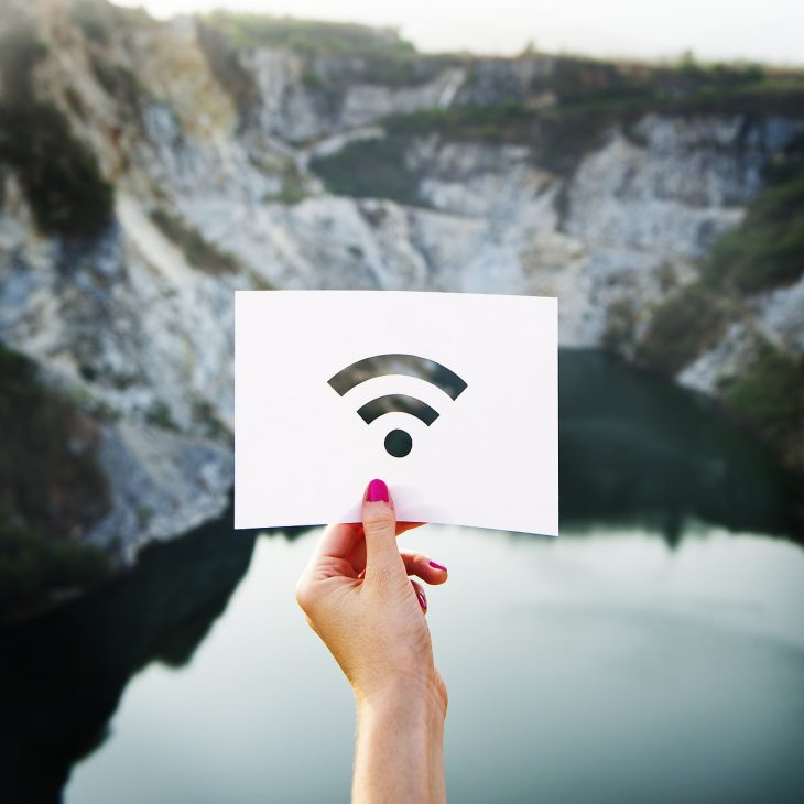 Paper with WiFi signal being held in front of a landscape