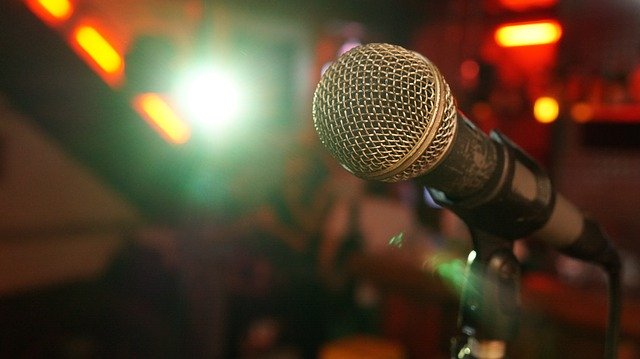 Microphone in front of a blurred audience and stage light by Pierre Rosa from Pixabay