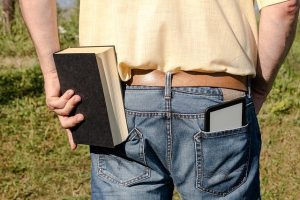 A person facing away from the camera with an ereader in their right back jeans pocket and trying to put a hardcover book in their left back pocket