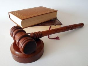 Gavel on pedestal with two books stacked in background