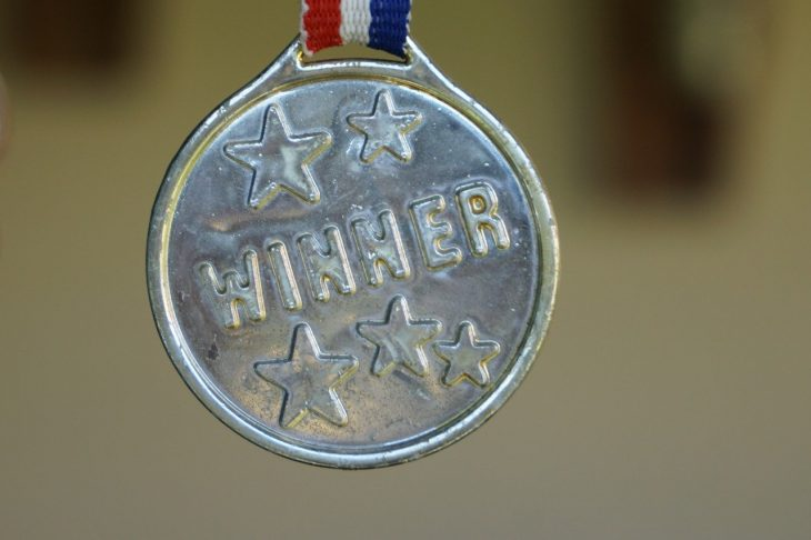 "Silver medal that says ""winner"" suspended by red white and blue ribbon"