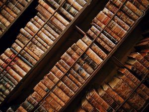 Old leather-bound books on diagonal shelves