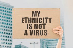 """Hand holding sign that reads """"My ethnicity is not a virus"""""""