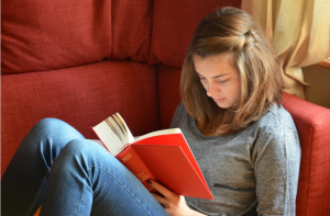 Teen girl reading red book, sitting on couch with knees up