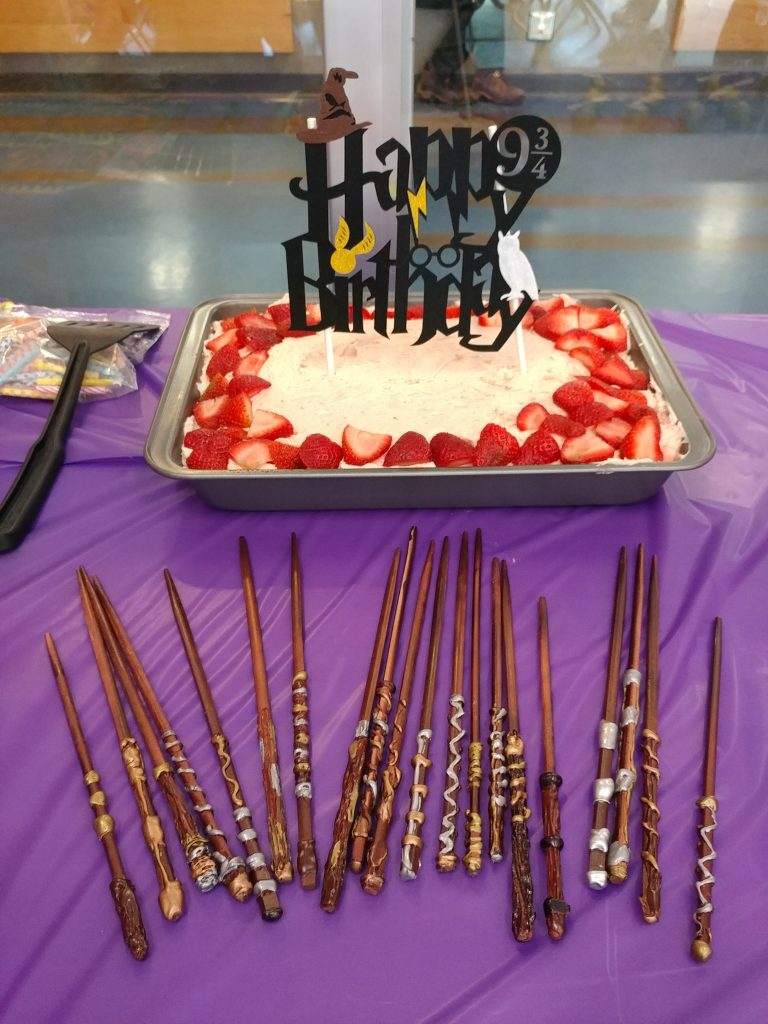 Homemade wands laying in front of a  happy birthday cake with a lightning bolt, snitch, owl, and wizard hat decorations atop the cake.