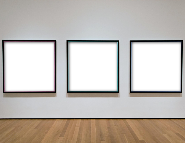 A row of three empty picture frames hanging on a white wall