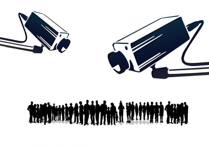 Silhouettes of people under surveillance cameras.