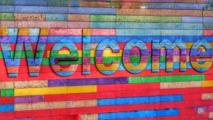 A colorful welcome sign painted on wood