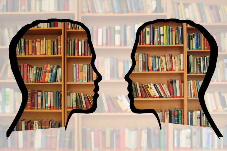 Stylized silhouettes of two people facing each other in front of library shelves.