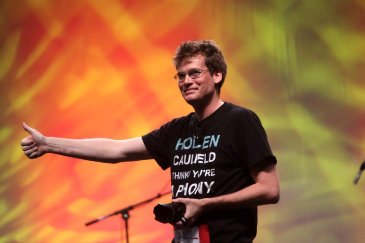 Photo of John Green on a stage, smiling and giving a thumbs up to the audience.