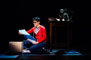 """Allison Mickelson as Alison in a production of the musical """"Fun Home"""". She is wearing a red sweatshirt with a black and white striped shirt underneath and jeans. She is kneeling next to a box looking at a stack of papers. A desk is behind her."""